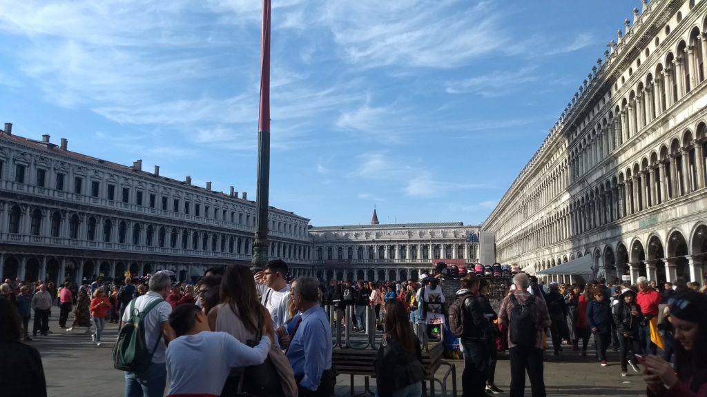 people bustle around piazza san marco
