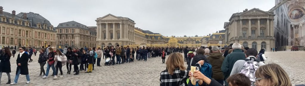 a queue of people waiting to get into versailles