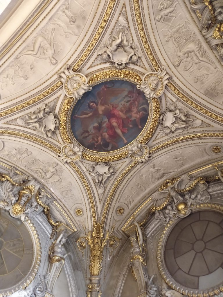 a white and gold decorative ceiling inside the louvre museum