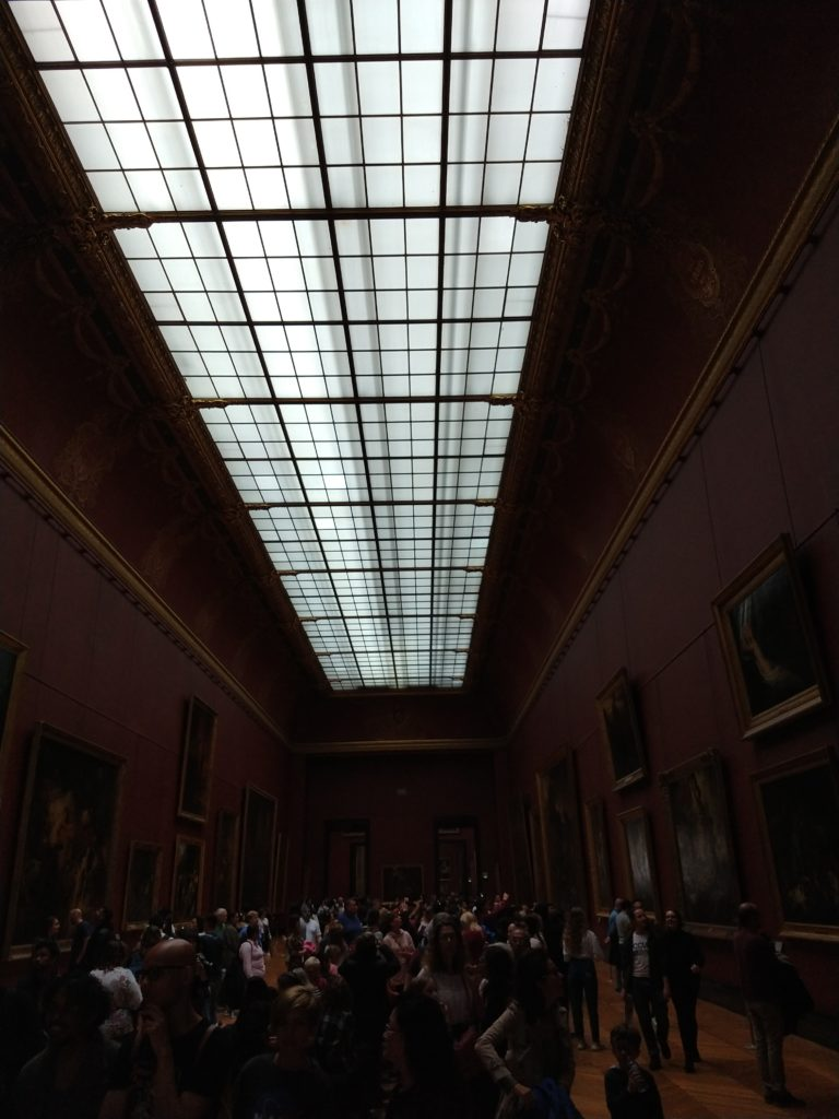 one of the many long galleries inside the louvre museum