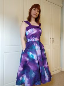 front view of michelle modelling the galaxy dress with her hands in the pockets