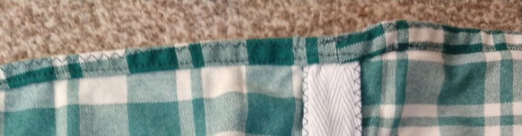 the inside of the chequered dress showing the hem and one of the side seams neatly bound