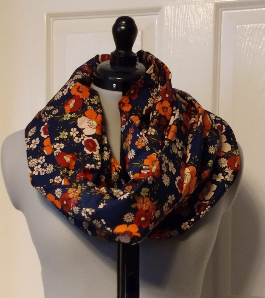 a navy blue snoody buff with an orange flower pattern