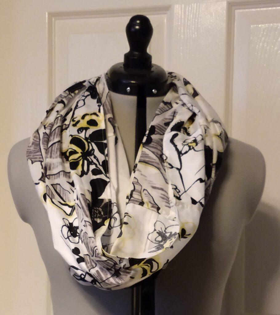 a white snoody buff with a yellow and black flower patchwork pattern